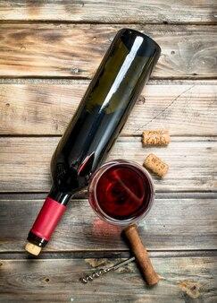 Rotwein in einem weinglas mit korkenzieher. auf einem holz.