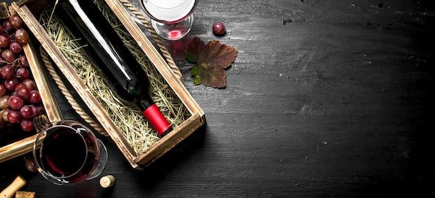 Rotwein in einer alten schachtel mit korkenzieher