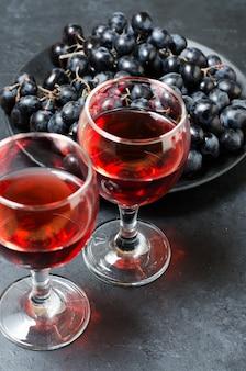 Rotwein in gläsern, eine reihe von schwarzen trauben