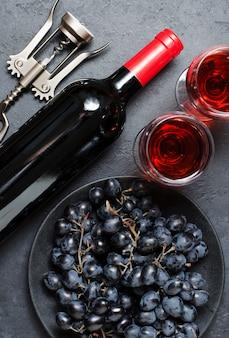 Rotwein in gläsern, trauben, eine flasche wein