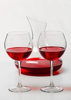 Rotwein in gläsern und karaffe auf weißer oberfläche