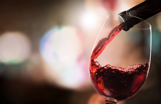 Rotwein in glas auf den hintergrund gießen