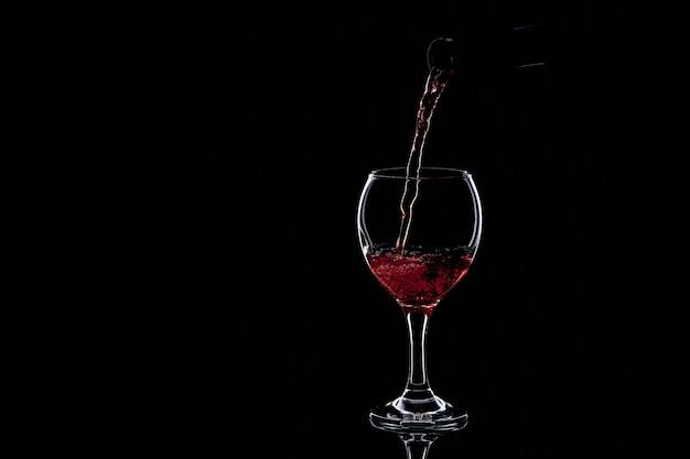 Rotwein in glas auf dunkelheit gießen. isolierte silhouette
