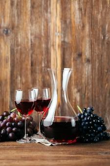 Rotwein in karaffe, zwei gläser und weintrauben auf holz