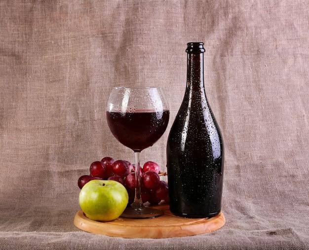 Rotwein, käse und trauben im stillleben.