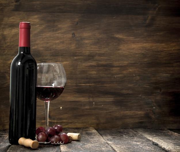 Rotwein mit einem zweig trauben und einem korkenzieher. auf einem hölzernen hintergrund.