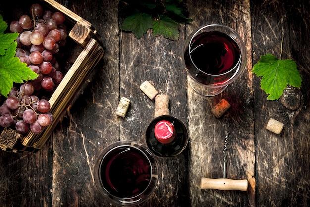 Rotwein mit einer schachtel trauben auf holztisch.