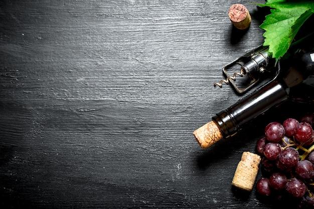 Rotwein mit korken und einem zweig trauben. auf einem schwarzen hölzernen hintergrund.