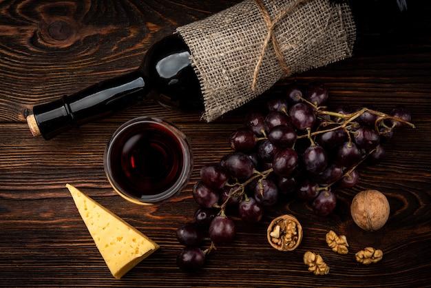 Rotwein, traube, käse und walnuss auf dunklem hölzernem hintergrund.