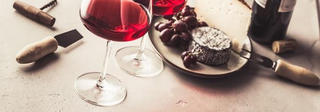 Rotwein und käse auf betonhintergrund
