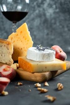 Rotwein und käse. verschiedene käsesorten mit nüssen, lavendel und feigenpfirsich auf schneidebrett. romantisches abendessen. kopieren sie platz für design. dunkler hintergrund. weicher fokus