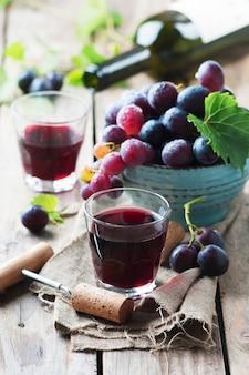 Rotwein und traube auf dem holztisch