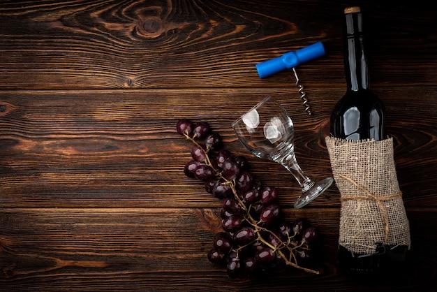 Rotwein und traube auf dunklem hölzernem hintergrund.
