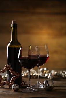 Rotwein und weihnachtsschmuck auf holztisch auf holzoberfläche
