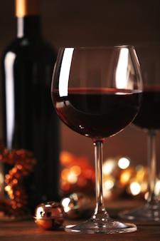Rotwein und weihnachtsschmuck auf holztisch auf holztisch