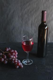 Rotwein und weinflasche mit trauben auf schwarz