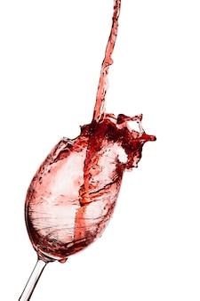 Rotwein wird auf weißem hintergrund in ein glas gegossen