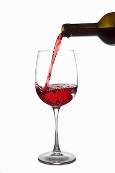 Rotwein wird aus einer flasche in ein glas gegossen, auf weißem hintergrund isolieren