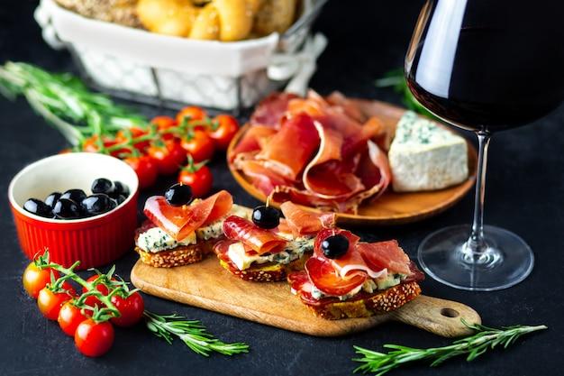 Rotwein wird in einen glockenkäse, in einen jamon, in einen prosciutto und in oliven auf einem schwarzen hintergrund gegossen. weinsnack auf einem hölzernen brett. brot mit käse- und weinsnacks. leckere snacks für die party.
