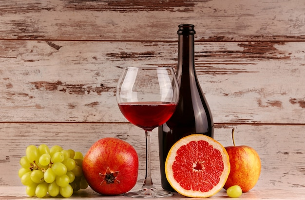 Rotweinflasche auf hölzernem hintergrund, apfel und granatapfel