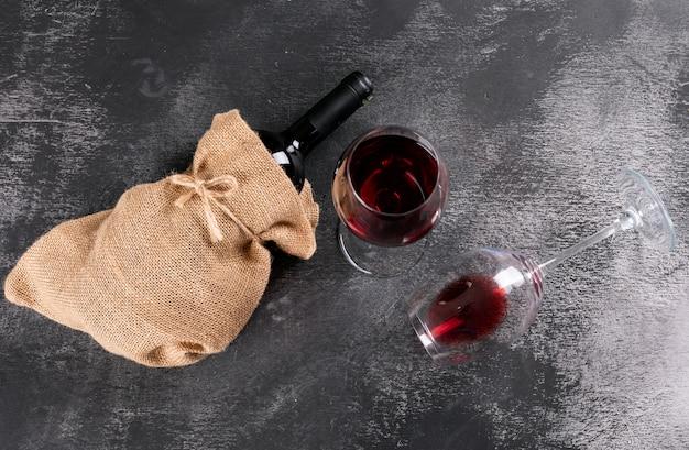 Rotweinflasche der seitenansicht in sackleinenbeutel auf schwarzem stein horizontal