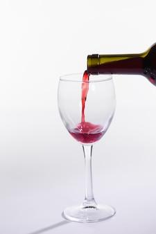 Rotweinflasche glas auf weiße oberfläche gießen
