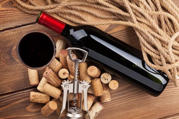 Rotweinflasche, glas, korken und korkenzieher. blick von oben über rustikalen holztischhintergrund
