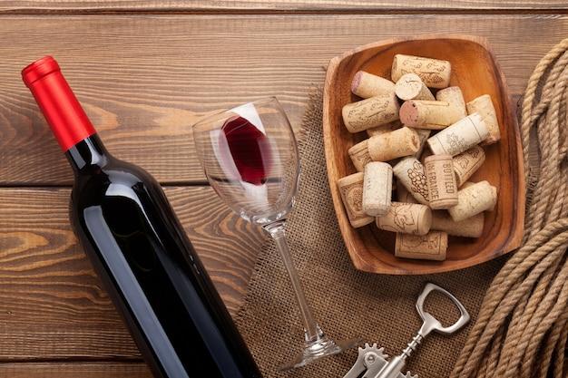 Rotweinflasche, glas wein, schüssel mit korken und korkenzieher. blick von oben über rustikalen holztischhintergrund