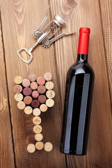 Rotweinflasche, glasförmige korken und korkenzieher. blick von oben über rustikalen holztischhintergrund