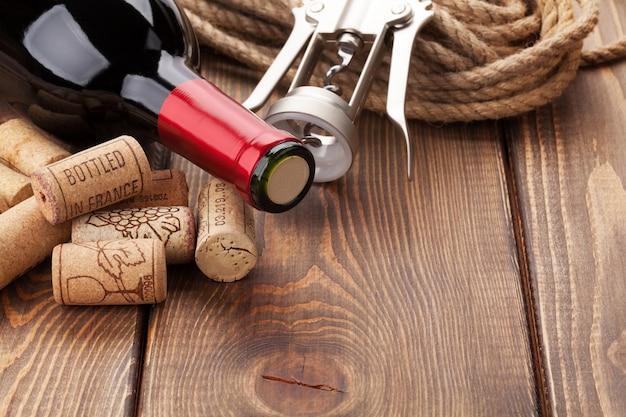 Rotweinflasche, haufen korken und korkenzieher über rustikalem holztischhintergrund mit kopienraum