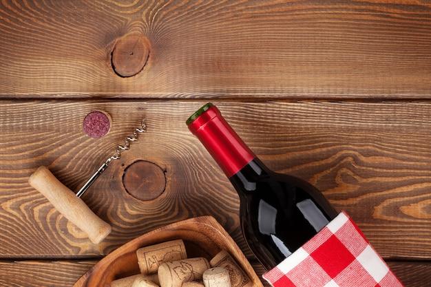 Rotweinflasche, schüssel mit korken und korkenzieher. blick von oben über rustikalen holztischhintergrund