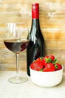 Rotweinflasche und glaserdbeere in weißer schüssel auf holzuntergrund