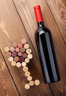 Rotweinflasche und glasförmige korken. blick von oben über rustikalen holztischhintergrund