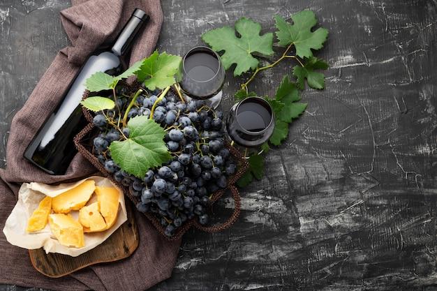 Rotweinflasche verschiedene käsetrauben. vintage stillleben weinkomposition mit camembert gealtertem käse, trauben. abendessen im restaurant, weinprobe auf dunklem betonhintergrund. langes webbanner.
