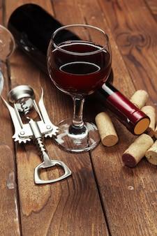 Rotweinflasche, weinglas und korkenzieher auf holztisch