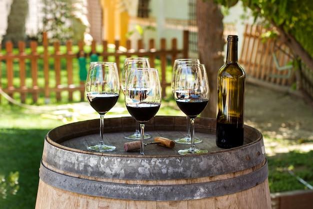 Rotweingläser und eine flasche auf einem fass im garten