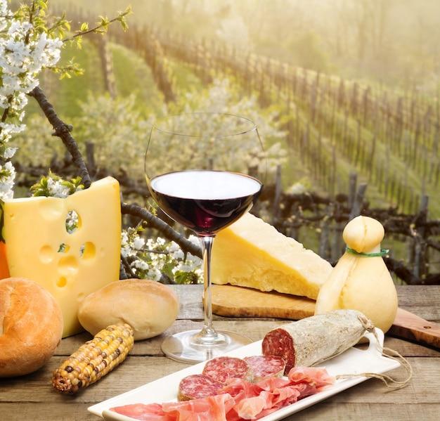 Rotweinglas mit käseauswahl gegen italienische collio weinberge