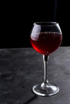 Rotweinglas mit langen schatten auf steintabelle. mit textfreiraum für ihren text