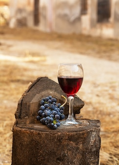 Rotweinglas und weintraube auf einem alten hölzernen hintergrund.