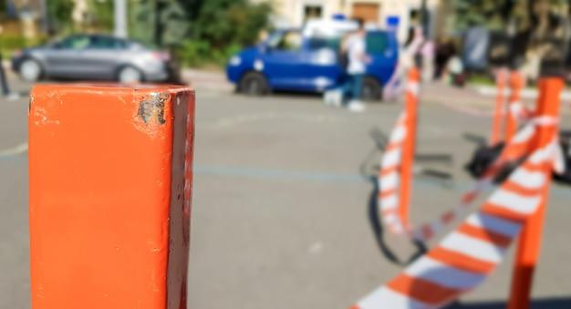 Rotweiß kreuzt nicht das band und die metallstange. signal rotes und weißes band, das an einem metallzaun hängt, gefahr, warnung. band und roter metallpfosten. verbotenes klebeband umschließt einen unsicheren bereich.