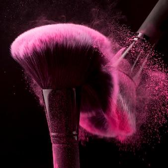 Rougebürsten, die rosa pulver auf schwarzem hintergrund zerstreuen