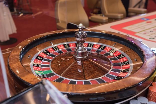 Roulette-tisch im casino, mit vielen spielen und slots, roulette-rad im vordergrund. goldenes und luxuriöses licht, casino-interieur. glücksspiel ist das wetten von geld oder das spielen von glücksspielen um geld