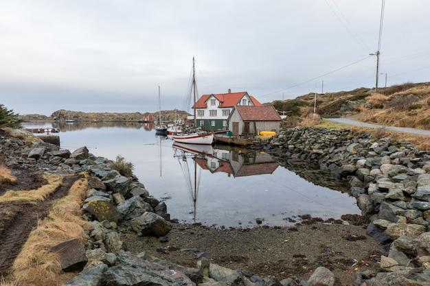 Rovaer in haugesund, norwegen - 11. januar 2018: der rovaer-archipel in haugesund, in der norwegischen westküste. boote, häuser und bootshäuser am meer.