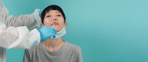 Rt-pcr-test. frau mit covid-19-abstrichtest. coronavirus-test während der epidemie. mediziner nehmen probe für virustests. blaugrüner hintergrund. arzt in psa-anzug-tupfer-test. virus-schnell-antigen-test.
