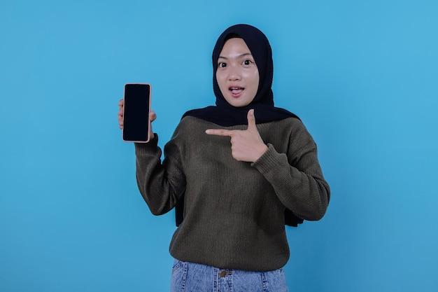 Rtrait der asiatischen schönen frau, die hijab trägt, bringt ein handy mit und das zeigen hat spaß und lächeln