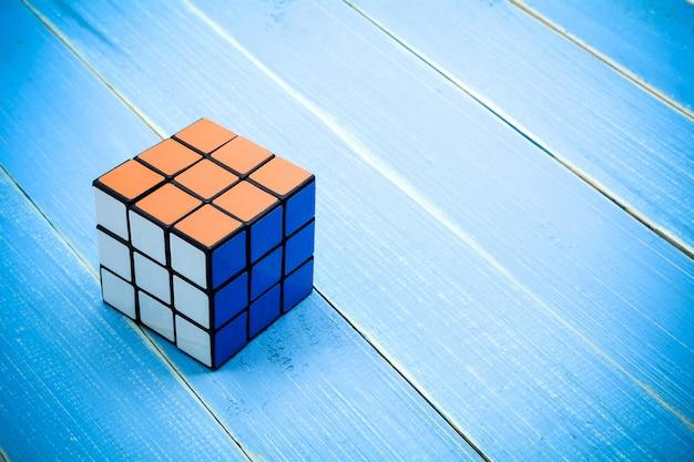 Rubiks würfel auf blauem hölzernem schreibtischhintergrund.