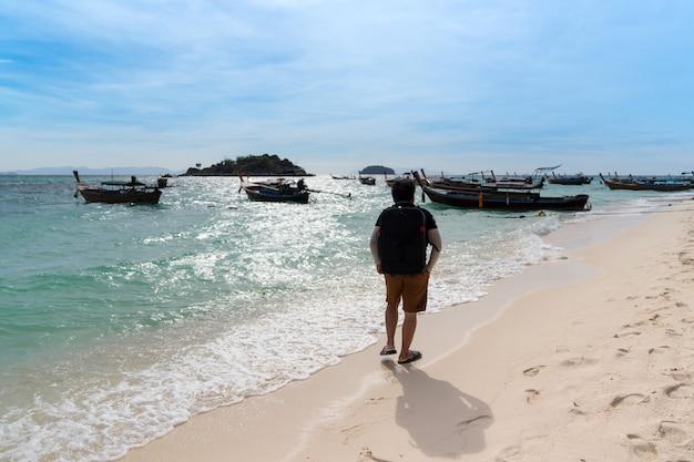 Rucksack asiatischer mann, der am sonnigen morgen mit vielen booten am weißen sandstrand des welligen blauen meeres entlang geht, sonnenlichtreflexion auf der wasseroberfläche, mann entspannt sich im sommer am strand auf den lipe-inseln, satun, thailand