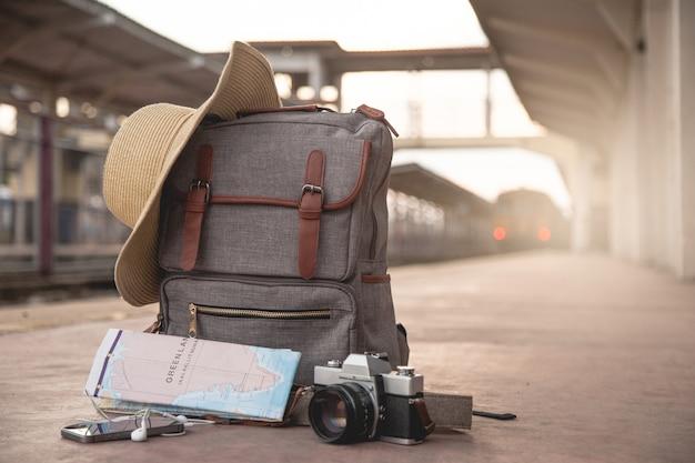 Rucksack, handy, kopfhörer, karte, hut und kamerafilm auf dem boden am bahnhof