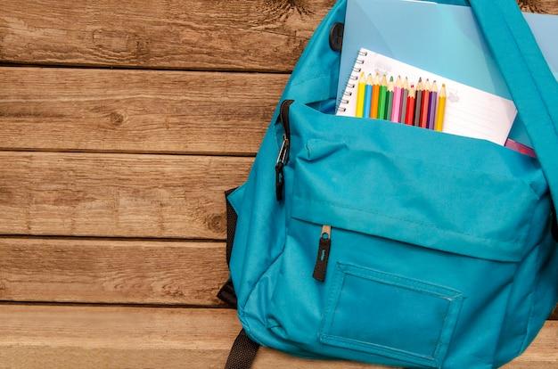 Rucksack mit bleistiften und notizbuch. vorderansicht der schultasche auf hölzernem brett.
