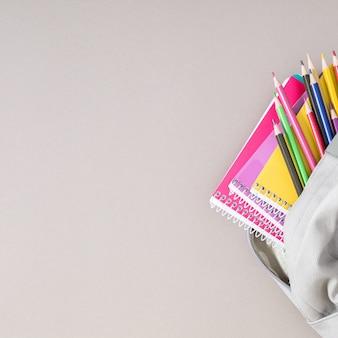 Rucksack mit bunten schulmaterialien auf grauem hintergrund zurück zur schule flach draufsicht